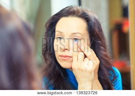 Young brunette woman holding contact lens on finger in front of her eye