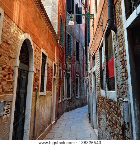 Narrow medieval street in historic part of Venice Italy