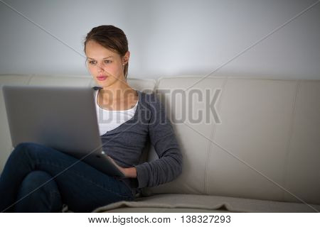 Pretty, young woman using her laptop computer at home, sitting on a sofa  (shallow DOF; color toned image)