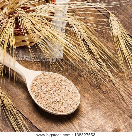 Wooden spoon filled with wheat bran near wicker basket with wheat ears on sackcloth napkin and wooden planks. Dietary supplement to improve digestion. Source of dietary fiber. Shallow depth of field