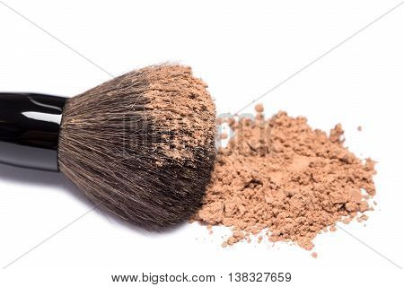 Close-up of large makeup brush with loose cosmetic powder on white background. Side view, shallow depth of field, focus on powdery brush tip