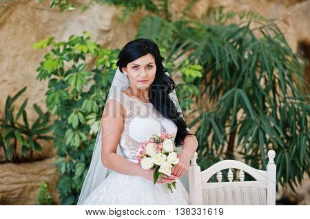 Temptation Model Brunette Bride At Exciting Wedding Dress Posed With Bouquet At Hands Near White Cha