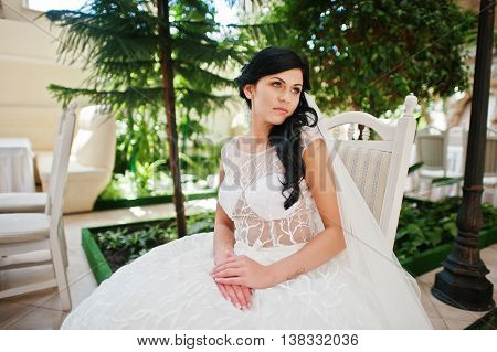 Temptation Model Brunette Bride At Exciting Wedding Dress Sitting On Chair Background Trees And Lant