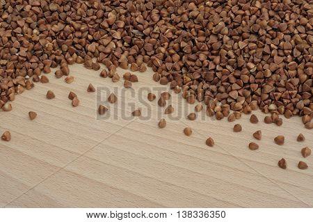 buckwheat scattered on a light wooden board