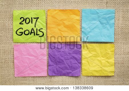 2017 New Year goals - handwriting on a sticky note against burlap canvas with blank notes