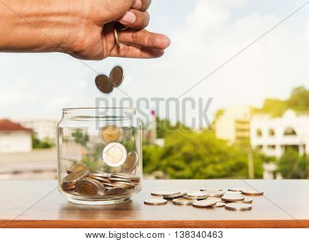 Close up glass bottle stacking silver coins falling on wooden table, Save money for prepare in the future