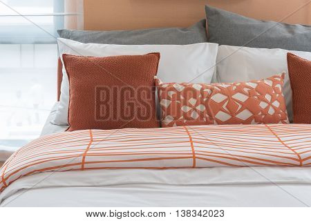 Orange Color Tone Pillows Set On Bed In Modern Bedroom