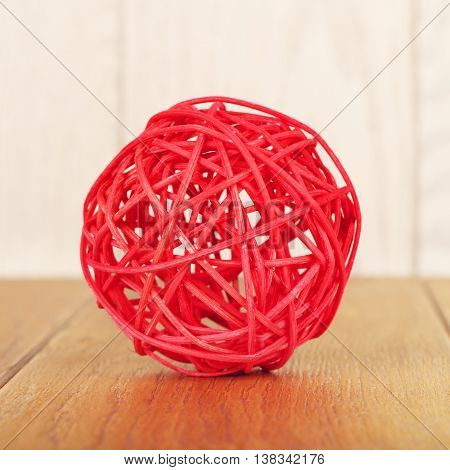 red rattan ball lying on wooden background
