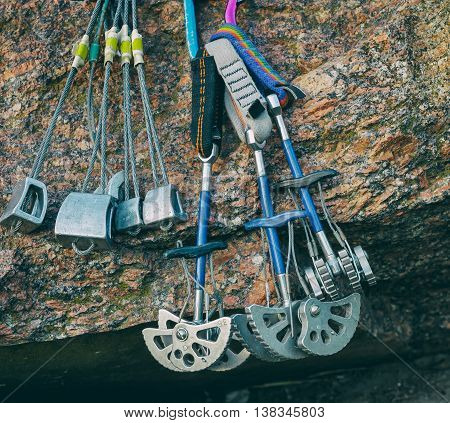 Equipment for mountaineering and rock climbing. On the granite stones. Slings with carbines set stoppers and friends