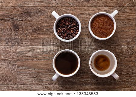 Four cups of coffee, phases of drink - bean, ground and empty cup.