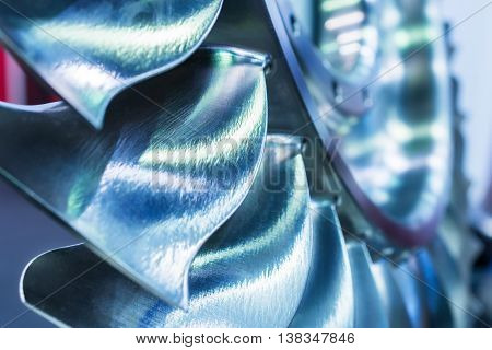 The blades of the turbine wheel, close-up shot. Toning in the color of cold metal. Shallow depth of field.