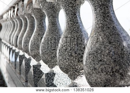Gray granite balusters elements closeup. Dark grey polished marble balustrade ta staircase, architectural detail background. Selective focus.
