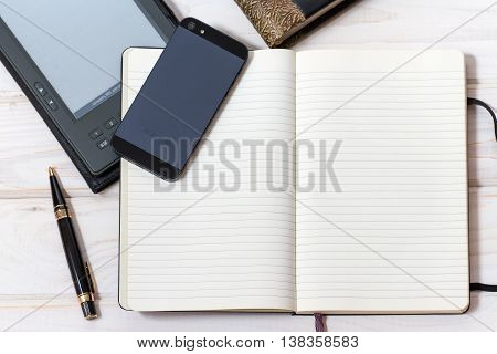 Phone, ebooks and note-book on the table.  An English translation is required for non-English text: Press ON to unblock
