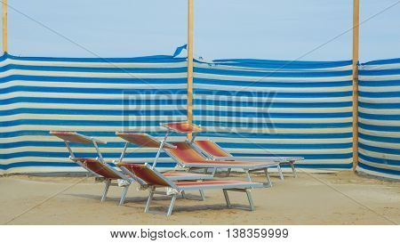 No people beach side with colorful deckchairs
