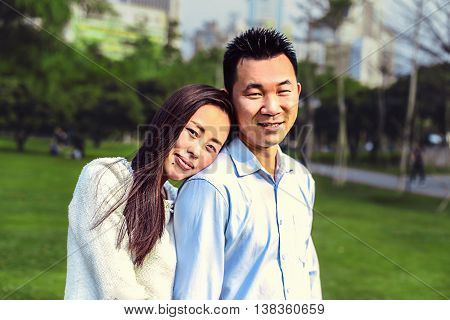 Chinese young couple in the park. Woman laid her head on the shoulder of her husband.