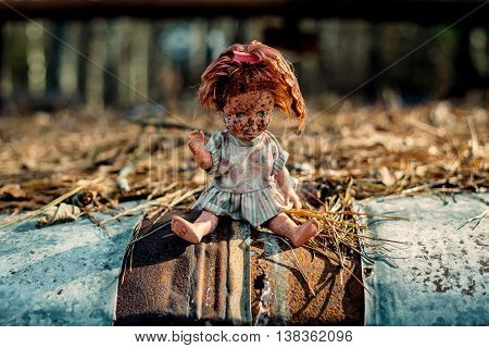 A doll sits on a rusting car