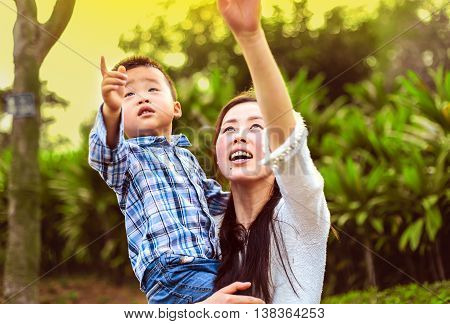 Chinese mother and child raised their hands up and show something. They walk in the park.