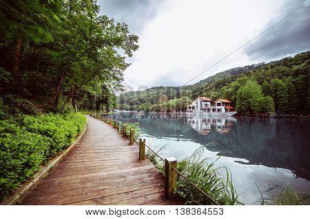 Pedestrian wooden walkway along the lake. Nice green plants.