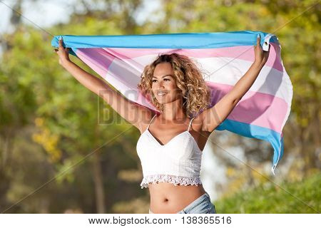 Mixed race transgender woman holding pride flag waving in the wind