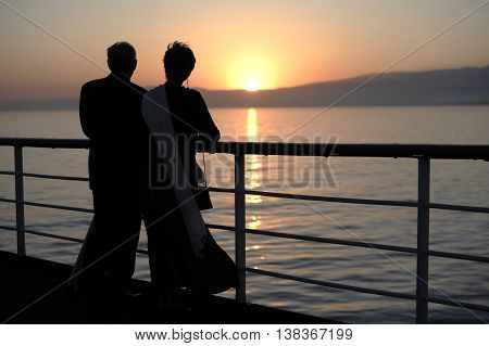 Older couple standing on the deck of a cruise ship at sunset