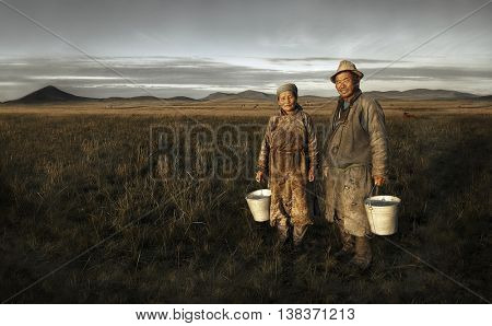 Mongolian couple farmers holding basin and posing in the field.