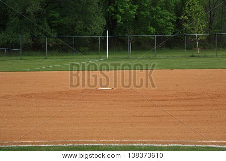 Baseball Pitching Rubber - Baseball field grassless infield pitching mound with rubber. With copy space.