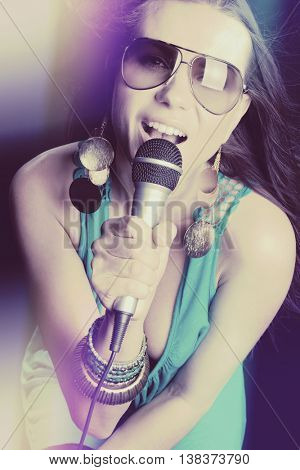 Beautiful popstar woman singing into microphone