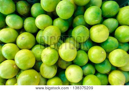 Fresh ripe limes green  in basket on wooden table