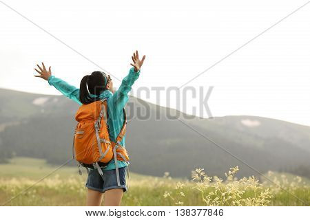 cheerying young woman hiker open arms to snow mountains in the distance