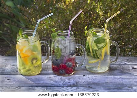 Three jars with fruit infused water on wooden table in summer garden