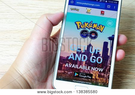 KOTA KINABALU MALAYSIA - 14 JULY 2016: Hands holding a smart phone with screen Pokemon Go website display its a mobile game developed by Niantic for iOS and Android devices.