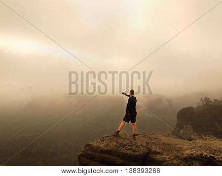 Ginger hair man in grey t-shirt and dark trekking trousers on sharp rock. Tourist with pole above misty valley. Sunny misty moment in rocky mountains.