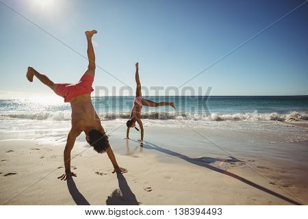 Couple performing somersault on beach in summer