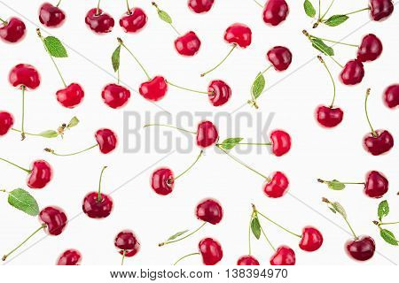 Scattered fresh ripe cherries with tails leaves on a white background. Cherry background. Fruit background.