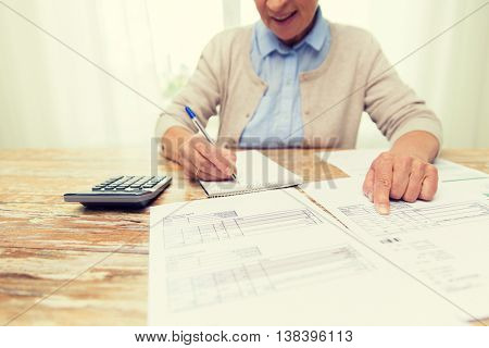 business, savings, annuity insurance, age and people concept - close up of senior woman with papers or bills and calculator writing at home