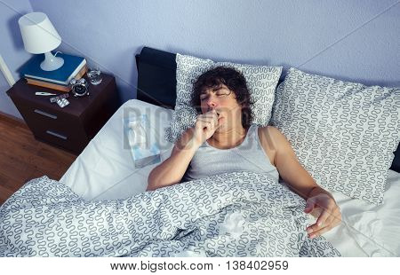 Portrait of young sick man coughing lying on bed. Sickness and healthcare concept.