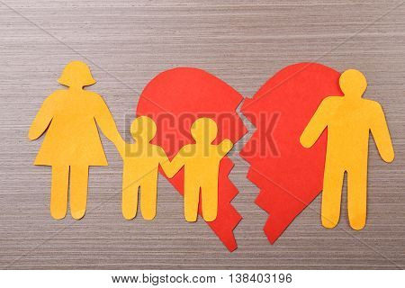 Paper family with broken heart on wooden table. Child custody concept