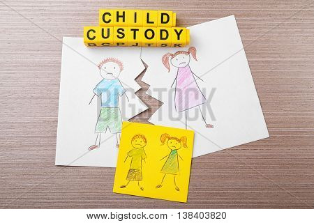 Torn drawing on wooden table. Child custody concept