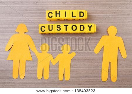 Paper family on wooden table. Child custody concept