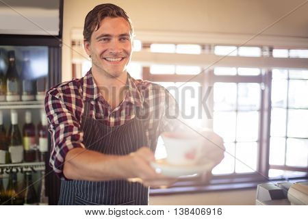Waiter serving cup of coffee at counter in café