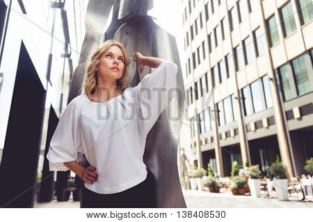 Attractive blonde woman looks up. Portrait on background of modern sculpture. Split toned photo