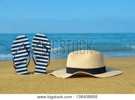 Flipflops and hat on a sandy ocean beach. Summer vacation concept.