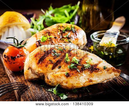 Marinated grilled healthy chicken breasts cooked on a summer BBQ and served with fresh herbs and lemon juice on a wooden board,