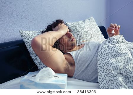 Young man with headache covering his head with hand palm while looking thermometer lying on bed. Sickness and healthcare concept.