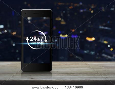 24 hours service icon on modern smart phone screen on wooden table over blur light city tower background Full time service concept
