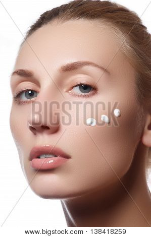 Beautiful Face Of Young Woman With Cosmetic Cream On A Cheek