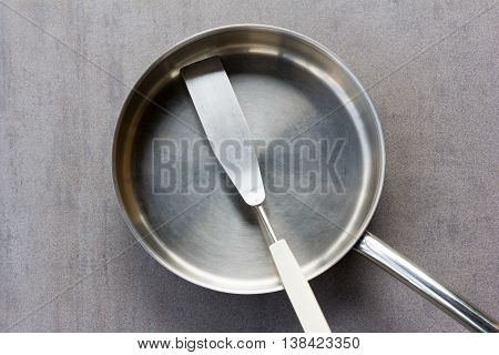 used clean empty stainless steel frying pan and spatula overhead view on the gray background closeup top view