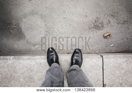 Male Feet Standing On Gray Curb