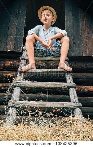 Boy sits on the ladder in hayloft