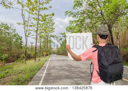Male tourist with Back packer and hat standing and looking at road map on road curve along with tropical forest.Concept forth coming trip and Preparing for a safe journey.